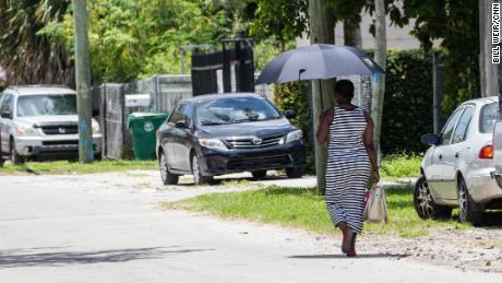 Seorang wanita menggunakan payung untuk berteduh saat dia berjalan di hari yang panas di Miami.
