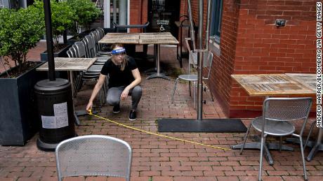Seorang karyawan yang mengenakan perisai pelindung menggunakan pita pengukur untuk memeriksa jarak antara meja dan kursi di area tempat duduk terbuka di sebuah restoran di Washington, D.C.