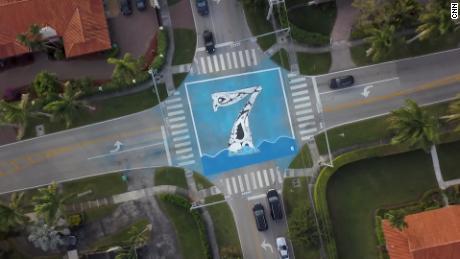 Di Pinecrest, seniman Xavier Cortada memasang mural yang menunjukkan berapa kaki di atas persimpangan permukaan laut.