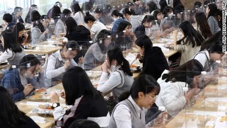 Para siswa makan siang di meja-meja yang dilengkapi dengan penghalang plastik untuk mencegah kemungkinan penyebaran virus corona baru di kantin di Sekolah Menengah Jeonmin di Daejeon, Korea Selatan, Rabu, 20 Mei.