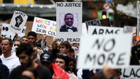 Para pengunjuk rasa berbaris di Queen Street di Auckland, Selandia Baru pada hari Senin.