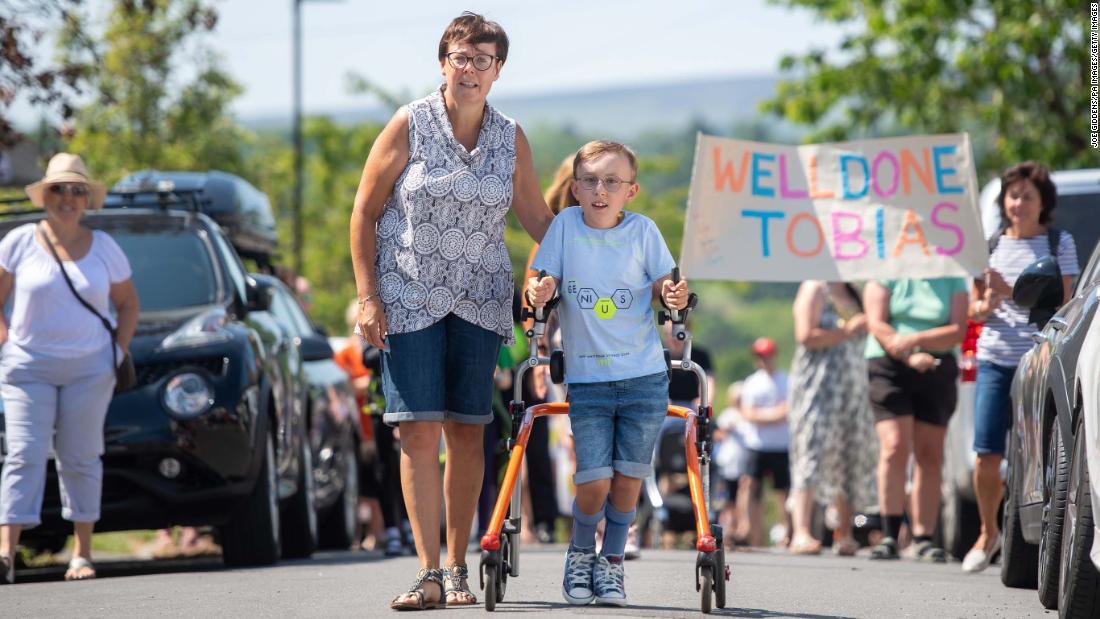 Tobias Weller, 9, yang memiliki cerebral palsy, menyelesaikan maraton amal di alat bantu jalannya