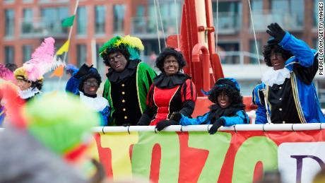 Orang-orang yang berpakaian seperti Pete Hitam tiba dengan perahu selama parade tradisional St. Nicholas pada 16 November 2019 di Den Haag, Belanda.
