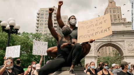 Demonstran mengenakan topeng saat mereka mengecam rasisme sistemik dan pembunuhan polisi terhadap orang kulit hitam Amerika di Washington Square Park di wilayah Manhattan pada 6 Juni 2020 di New York City.