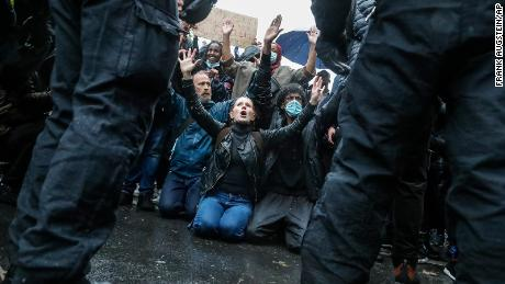Demonstran berlutut menghadap petugas polisi dalam pawai Black Lives Matter lainnya di London, Sabtu.