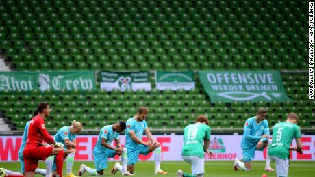 Para pemain dari kedua tim berlutut untuk memprotes sebelum pertandingan Bundesliga antara SV Werder Bremen dan VfL Wolfsburg di Jerman pada hari Minggu.
