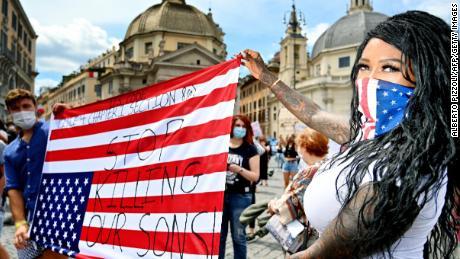 Pengunjuk rasa memegang bendera AS terbalik di Roma.