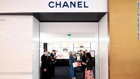Asisten toko menyambut pelanggan ke Chanel di Galeries Lafayette, pada hari pertama pembukaan kembali department store di Paris pada bulan Mei.