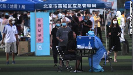 Seorang petugas kesehatan yang mengenakan pakaian pelindung mengambil tes usap dari seorang wanita di pusat pengujian yang didirikan untuk orang-orang yang mengunjungi atau tinggal di dekat pasar Xinfadi di Beijing.