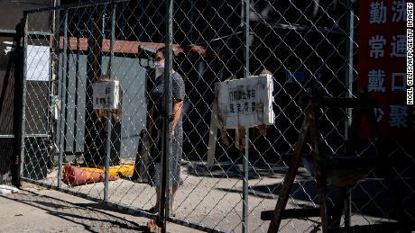 Seorang wanita berdiri di belakang pagar ketika dia menunggu pengiriman barang yang dia pesan secara online di area perumahan di bawah penguncian dekat pasar Xinfadi yang ditutup di Beijing.