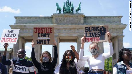 Orang-orang menghadiri rapat umum menentang rasisme di depan Gerbang Brandenburg di Berlin pada hari Minggu.