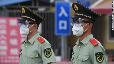 Petugas polisi paramiliter mengenakan topeng dan kacamata saat mereka berjaga di pintu masuk ke pasar Xinfadi yang ditutup di Beijing pada 13 Juni.
