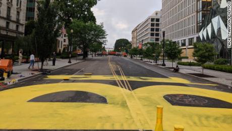 """Pekerja kota mulai melukis """"kehidupan hitam itu penting"""" dengan cat kuning pada hari Jumat di 16th Street di Washington, D.C."""